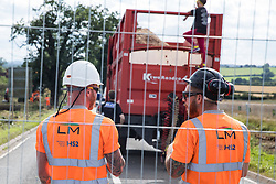 Offchurch, UK. 24th August, 2020. HS2 workers stand and chat after an anti-HS2 activist occupied a trailer transporting wood chip in order to try to prevent or delay tree felling alongside the Fosse Way in connection with the HS2 high-speed rail link. The controversial HS2 infrastructure project is currently expected to cost £106bn and will destroy or significantly impact many irreplaceable natural habitats, including 108 ancient woodlands.