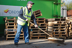 Man with a mild learning disability working as a factory cleaner, shown here sweeping, helped into employment by the Ready 4 Work team, Nottinghamshire County Council