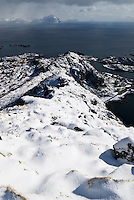View from snow covered mountain above Stamsund to distant distant mountain peaks, Vestvagoy, Lofoten islands, Norway