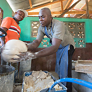 CAPTION: After milling, the cassava is put into a press so that all the moisture can be removed. Currently, the cassaverie is thriving, and plans for the adjoining bakery to open are developing apace. Once it's operational, OGKPS will produce white bread, manioc bread, and other cassava products, and will also provide manioc milling services. ORGANIZATION: Organizasyon Gwoupman Kominotè Pawas Sakretè (OGKPS). LOCATION: #88 Laviolette (Monte Pa Desann), Cap-Haïtien, Haiti. INDIVIDUAL(S) PHOTOGRAPHED: Jean-Pierre Regel (left) and Elino Selondieu (right).