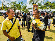 20 OCTOBER 2016 - BANGKOK, THAILAND:  A vendor, right, sells flowers to people mourning the death of Bhumibol Adulyadej, the King of Thailand, at Sanam Luang. Sanam Luang, the Royal Ceremonial Ground, is packed with people mourning the Monarch's death. The King died Oct. 13, 2016. He was 88. His death came after a period of failing health. Bhumibol Adulyadej was born in Cambridge, MA, on 5 December 1927. He was the ninth monarch of Thailand from the Chakri Dynasty and is also known as Rama IX. He became King on June 9, 1946 and served as King of Thailand for 70 years, 126 days. He was, at the time of his death, the world's longest-serving head of state and the longest-reigning monarch in Thai history.      PHOTO BY JACK KURTZ