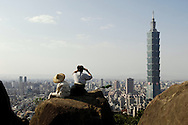Two people sit a watch the sunset on Elephant Mountain in Taipei, Taiwan.