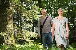 Portrait of mature couple walking in forest, smiling