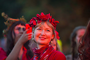 Glastonbury Festival, 2015.<br /> Women with red flowers in her hair from a festival choir, smiling, dressed in red, launching the start of the Glastonbury Festival
