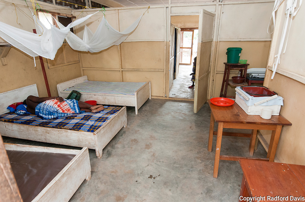 In-patient beds. Here, a woman has been in the clinic for a few days now with a fever of unknown origin. The Community Health Officer in charge believes she might have Lassa Fever. They cannot do anymore for her. The clinic has no way to diagnose the disease. There are no antibiotics for adults in the clinic, only children.