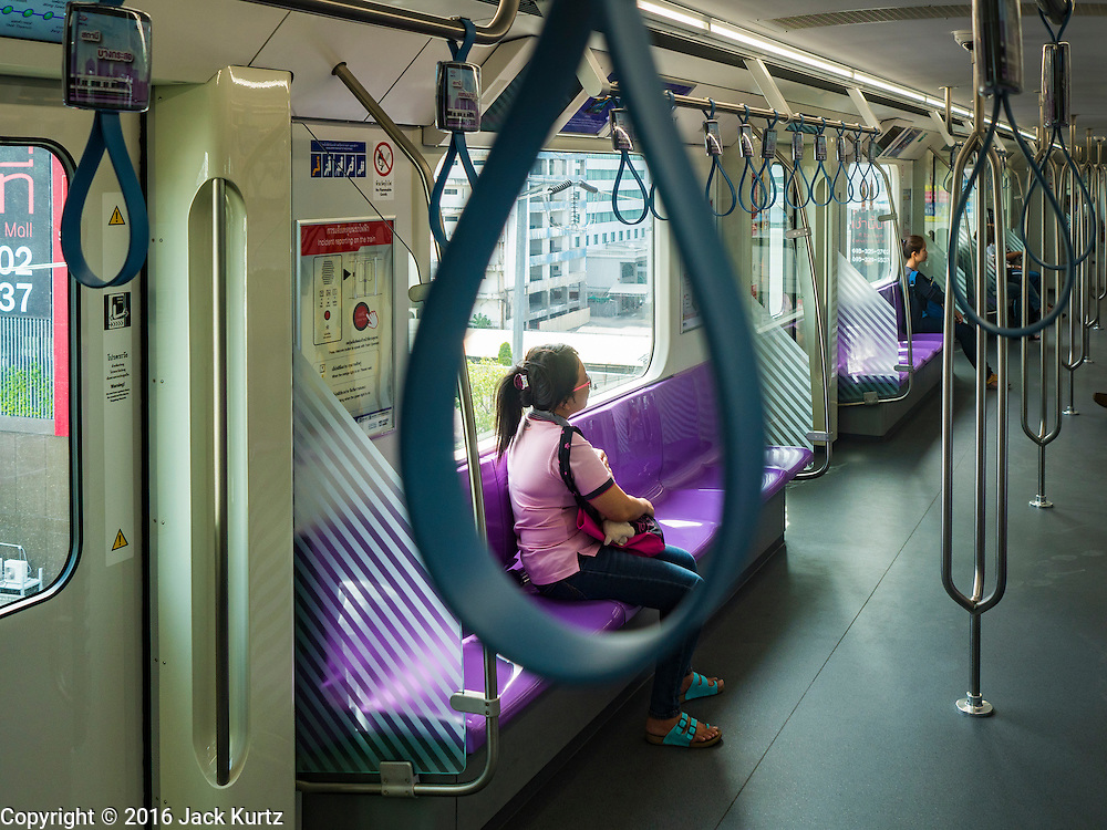 """23 AUGUST 2016 - NONTHABURI, NONTHABURI, THAILAND: Passengers in a nearly empty train car on the """"Purple Line,"""" the new Bangkok commuter rail line that runs from Bang Sue, in Bangkok, to Nonthaburi, a large Bangkok suburb. The Purple Line is run by the  Metropolitan Rapid Transit (MRT) which operates Bangkok's subway system. The Purple Line is the fifth light rail mass transit line in Bangkok and is 23 kilometers long. The Purple Line opened on August 6 and so far ridership is below expectations. Only about 20,000 people a day are using the line; officials had estimated as many 70,000 people per day would use the line. The Purple Line was supposed to connect to the MRT's Blue Line, which goes into central Bangkok, but the line was opened before the connection was completed so commuters have to take a shuttle bus or taxi to the Blue Line station. The Thai government has ordered transit officials to come up with plans to increase ridership. Officials are looking at lowering fares and / or improving the connections between the two light rail lines.     PHOTO BY JACK KURTZ"""