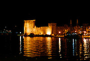 Fortress Kamerlengo floodlit at night,with boat moored at waterfront and reflections in water. Trogir, Croatia