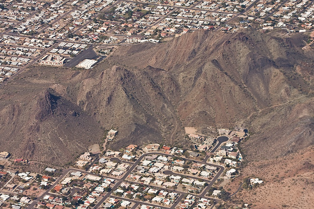 Aerial view of upper class residential homes up against bare hillsides in the outskirts of Phoenix, Arizona.