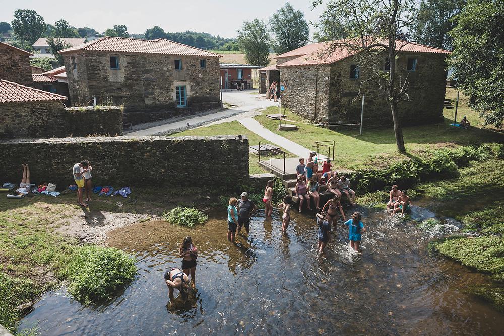 After a few hot hours of walking, people enjoy the cool stream that flows past the municipal albergue in Ribadiso da Baixo, Spain. (July 9, 2018)<br /> <br /> DAY 43: PALAS DE REI TO RIBADISO DA BAIXO -- 26 KM