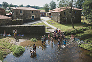 After a few hot hours of walking, people enjoy the cool stream that flows past the municipal albergue in Ribadiso da Baixo, Spain. (July 9, 2018)<br />