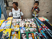 17 OCTOBER 2016 - BANGKOK, THAILAND: A woman and her son sell portraits of Bhumibol Adulyadej, the late King of Thailand, from a table near Sanam Luang in central Bangkok. Thai King Bhumibol Adulyadej died Oct. 13, 2016. He was 88. His death comes after a period of failing health. Bhumibol Adulyadej, was born in Cambridge, MA, on 5 December 1927. He was the ninth monarch of Thailand from the Chakri Dynasty and is also known as Rama IX. He became King on June 9, 1946 and served as King of Thailand for 70 years, 126 days. He was, at the time of his death, the world's longest-serving head of state and the longest-reigning monarch in Thai history.        PHOTO BY JACK KURTZ