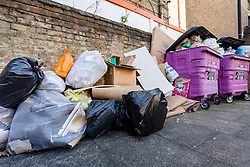 © Licensed to London News Pictures. 22/03/2020. London, UK. Overflowing communal domestic rubbish bins are seen outside blocks of flats in east London today, as the coronavirus outbreak continues to escalate in the capital. Recent media reports have stated that some local councils plan to cancel certain types of rubbish collections to help stop the spread of coronavirus. Photo credit: Vickie Flores/LNP