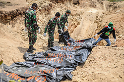 October 4, 2018 - Palu, Central Sulawesi, Indonesia - (EDITORS NOTE: Image depicts death.) Officers placing the bodies of victims in grave holes before being mass-buried in Poboya. A deadly earthquake measuring 7.7 magnitude and the tsunami wave caused by it has destroyed the city of Palu and much of the area in Central Sulawesi. According to the officials, death toll from devastating quake and tsunami rises to 1,347, around 800 people in hospitals are seriously injured and some 62,000 people have been displaced in 24 camps around the region. (Credit Image: © Hariandi Hafid/SOPA Images via ZUMA Wire)