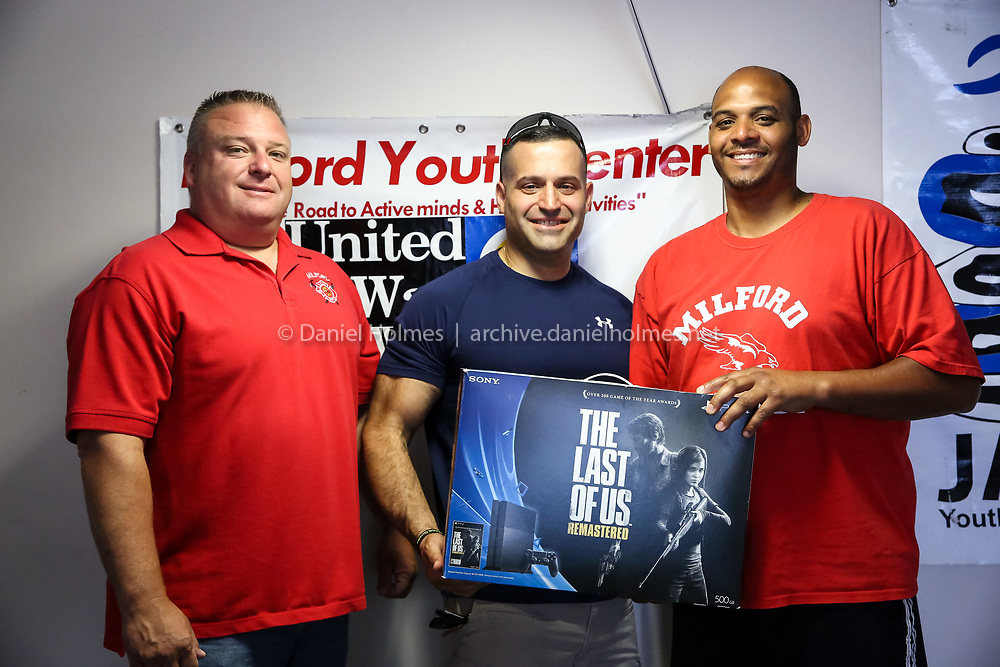 (6/26/15, MILFORD, MA) From left, Sean Meehan of the Milford Permanent Firefighters Association, police union President Robbie Tusino, and Youth Center Director Sidney DeJesus pose for a photo with a Sony Playstation 4 at the temporary location Youth Center  at Congress St. in Milford on Friday. The fire and police departments donated the Sony Playstation 4 to replace one that was stolen. Daily News and Wicked Local Photo/Dan Holmes