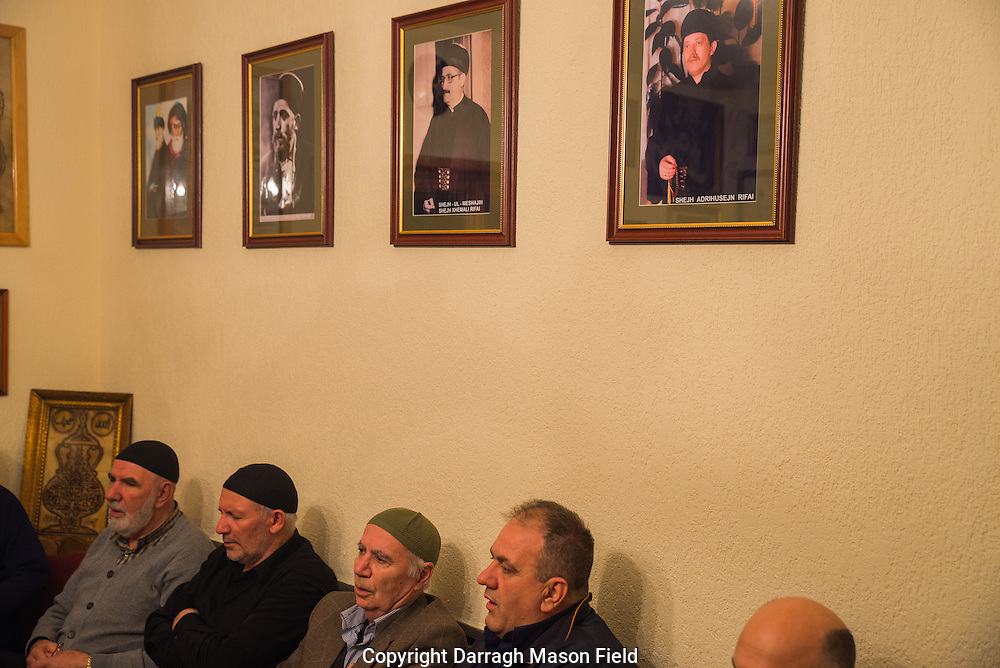 Sufi's sit in audience with the Shejh. Above their heads are portraits of Sufi saints and current and previous Shejh.