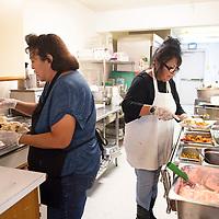 Crownpoint Senior Center cook Joann Morgan, left, and Crownpoint Senior Center supervisor Bess Seschillie serve  Thanksgiving dinner at the Crownpoint Senior Center, Thursday, Nov. 21.