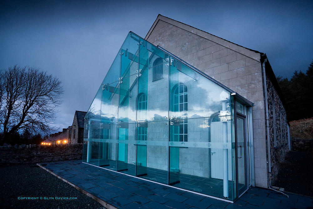 An historic Welsh Chapel nestling into a dark Welsh mountainside faces the Irish Sea. Twilight clouds race past as reflections in the new glass vestibule, designed to allow visitors to stand in warmth and comfort from the Chapel, whilst watching the sea and the weather change in front of them.