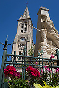 Patriotic village war memorial with well-tended flowers and local church, on 25th May, 2017, in Homps, Languedoc-Rousillon, south of France.
