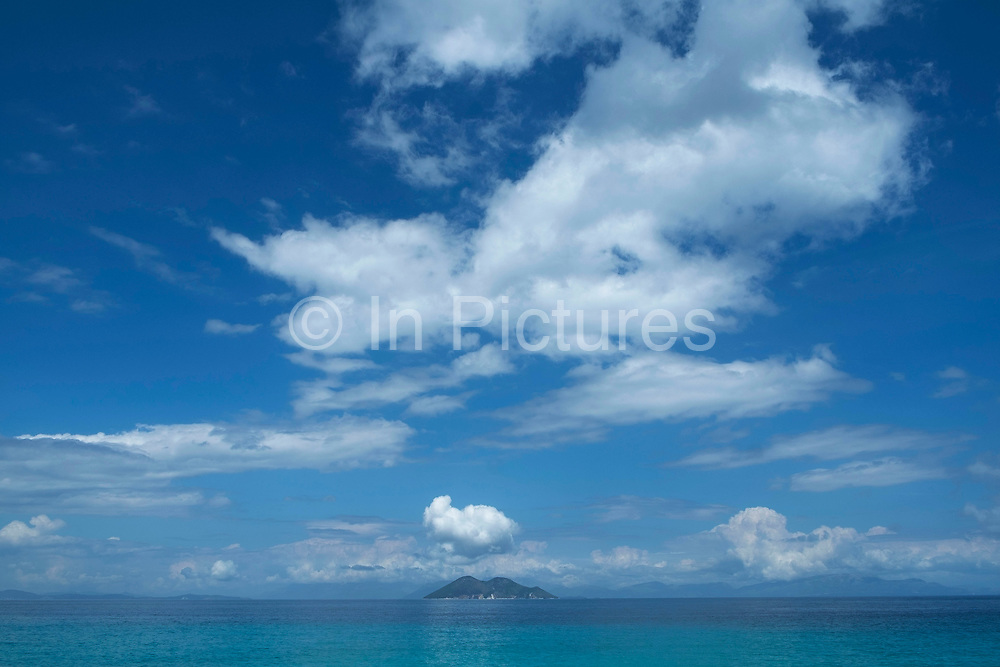 Blue sky with clouds view towards the island of Atokos at Gidaki beach near Vathy, Ithaca, Greece. Ithaca, Ithaki or Ithaka is a Greek island located in the Ionian Sea to the west of continental Greece. Ithacas main island has an area of 96 square kilometres. It is the second-smallest of seven main Ionian Islands.