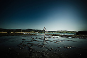 Surfer, early morning reflected in rockpool, Gerringong, NSW, Australia