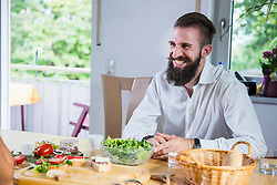 Young man sitting at kitchen table and smiling, Bavaria, Germany