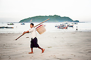 Myanmar, Ngapali. Man walks with a basket.<br /> Every single morning all the fisherman from the little village at Ngapali Beach come back home with their night catch. At the beach all the women wait for them and afterwards work with drying and selling fish and other creatures from the sea begins.