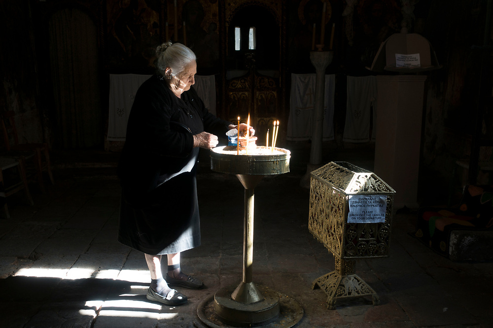 A woman lights candles in Saint Nicholaos (Nicolas) church, in the coastal village of Petra. S. Nicholaos, patron of those who go out to the sea, is the Islands main saint. It seems that the people of the Island have an inseparable bond with whatever the sea provides them- For better or worse.