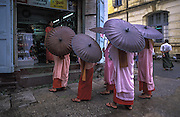 Buddhist nuns collect alms from shopkeepers in downtown Yangon.