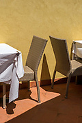 Tables and chairs at a restaurant in Boccadasse near Genoa, Italy. Boccadasse is a fishing village that has, despite its proximity to Genoa, managed to retain its charm and is very popular as a dining and swimming destination with Italian tourists.