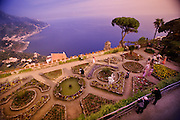 A beautiful garden filled with tourists on an Italian cliffside