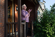 As the number of UK deaths from Coronavirus reaches 37,837, a further 377 in the last 24hrs a grandmother stands outside her house to clap for the NHS National Health Service key worker heroes for the last time during the UK Coronavirus pandemic lockdown, on 28th May 2020 in London, England.