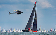 A media helicopter tracks the biggest monohull in the fleet, Comanche at the start of the 90th anniversary Rolex Fastnet Race on the Solent. A record fleet of 370 yachts will compete to win the Fastnet Challenge Cup.<br /> The 600 nautical mile race starts in Cowes, Isle of Wight, heading to the Fastnet Rock off the south west coast of Ireland and finishes in Plymouth.<br /> It is the world's biggest offshore race with 75% amateur sailors and professional yachtsmen competing against each other. <br /> Picture date Sunday 16th August, 2015.<br /> Picture by Christopher Ison. Contact +447544 044177 chris@christopherison.com