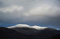 Dramatic mountain light over snow covered peak from Alesjaure mountain huti, Kungsleden trail, Lappland, Sweden