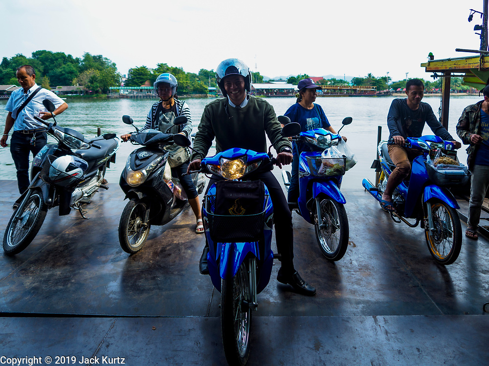 """09 JANUARY 2019 - KANCHANABURI, THAILAND:  Motorcyclists riding a ferry across the River Kwai leave the ferry it docked on the west side of the river. The ferry goes across the River Kwai downriver from downtown Kanchanaburi, the site of the famous """"Bridge on the River Kwai."""" Small ferries like this, once common on Thai river crossings, are disappearing because Thailand has dramatically improved its infrastructure since this ferry started operating about 50 years ago. The ferry operator said his grandfather started the ferry, with a small raft he would pole across the river, in the late 1960s. Now his family has a metal boat with an inboard engine. There are large vehicle bridges across the river about 5 miles north and south of this ferry crossing, but for people in rural communities on the west side of the river the ferry is still the most convenient way to cross the river.     PHOTO BY JACK KURTZ"""