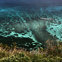 Small craft races over the reef of Dravuni. Island, Fiji