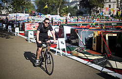 © Licensed to London News Pictures. 07/05/2018. London, UK. A cyclist in the early morning sunshine at day three of the Canalway Cavalcade festival takes place in Little Venice, West London on Monday, May 7th 2018. Today is expected to be the hottest May bank holiday Monday on record. Photo credit: Ben Cawthra/LNP