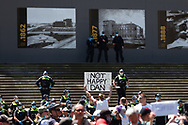 """A man holds up a 'Not Happy Dan"""" placard to police on the steps of parliament during the Melbourne Freedom Rally at Parliament House. Police move into position on the steps of state parliament ahead of a planed protest. The groups who have organised the many Freedom Day protests over the last 3 months, attempted to march on State Parliament during Melbourne Cup Day demanding the sacking of Premier Daniel Andrews for the lockdown and attacks on their civil liberties. Police met with the protester's with significant force despite the city having had zero cases for five days. (Photo by Dave Hewison/Speed Media)"""
