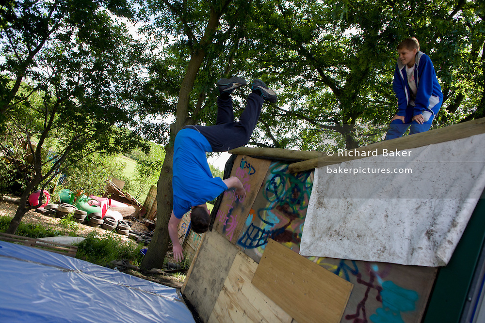 Boy somersults off container in risk averse playground called The Land on Plas Madoc Estate, Ruabon, Wrexham, Wales.