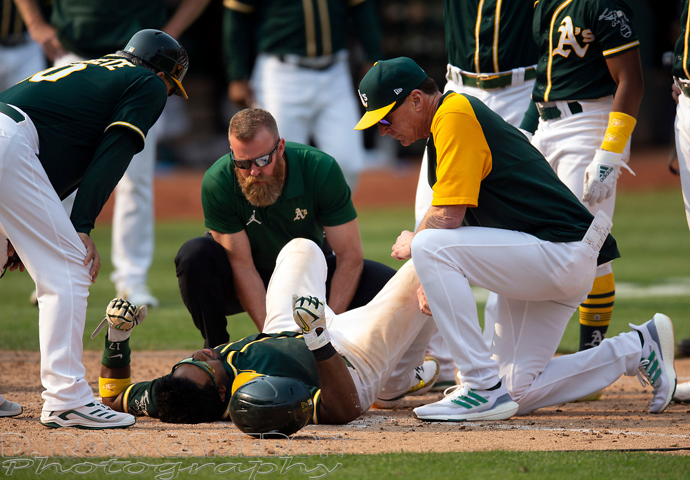Sep 25, 2021; Oakland, California, USA; The Oakland Athletics trainer, center facing, and manager Bob Melvin, right, tend to Elvis Andrus after he fell to the ground with an injury while scoring the winning run against the Houston Astros during the ninth inning at RingCentral Coliseum. Mandatory Credit: D. Ross Cameron-USA TODAY Sports