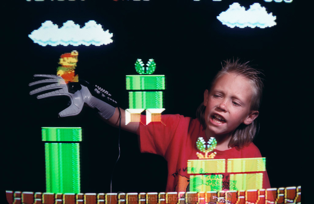 Virtual reality videogame: Jack Menzel wears a Nintendo Power Glove to interact with the fictional (or virtual) Super Mario Brothers (Nintendo characters) in the living room of his home in Napa, California. Model Released (1990)