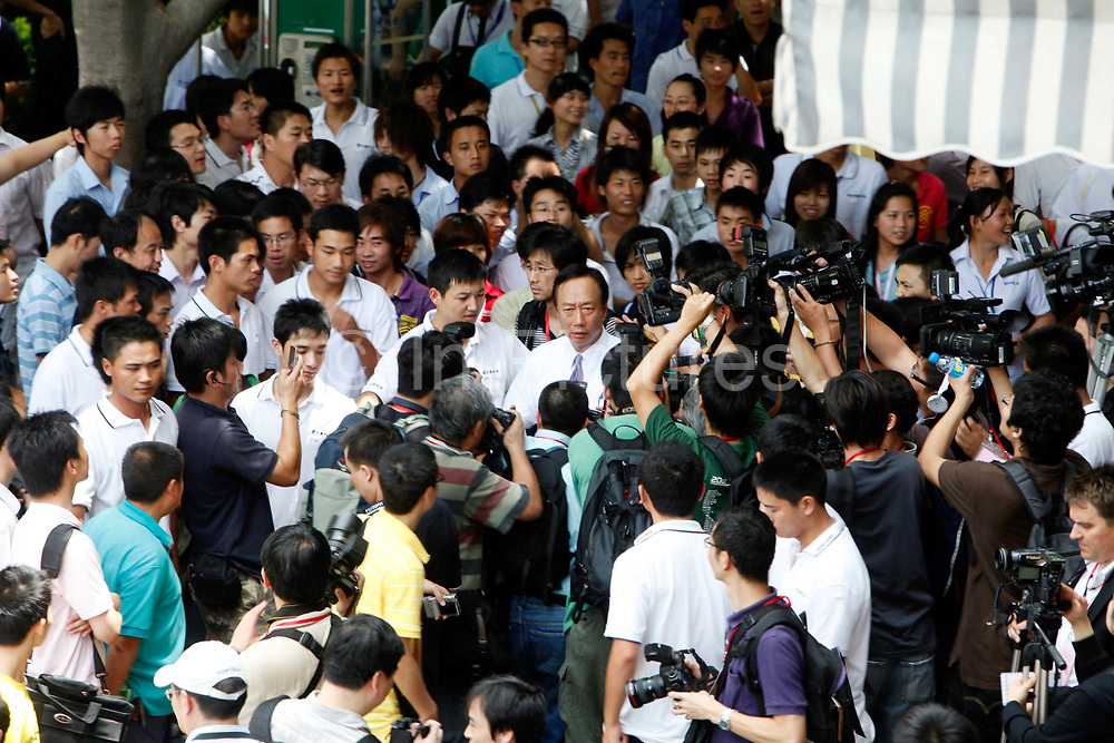Terry Gou, founder and chairman of Hon Hai Group and one of the richest man in Taiwan, center, is surrounded by the media at the company's Foxconn plant in Shenzhen, China, on Wednesday, May 26, 2010. Hon Hai is the parts supplier for many hi-tech companies around the world including Apple Inc., Hewlett-Packard Co. and Dell Inc. There have been 12 suicides at the company's 300 thousand employee strong factory complex in Shenzhen so far this year. Foxconn has since moved some of its operations further inland to be closer to labor pool as well as cut costs.