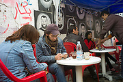 Couples sit at pavement cafe called the Revolution of the 25th of January in the Bourse area of Cairo. Behind them are graffiti portraits of young men killed in the fighting, Cairo, Egypt