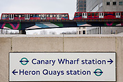 Street sign for Canary Wharf and Heron Quays DLR stations outside Canary Wharf tube station in London, England, United Kingdom.  A Docklands Light Railway (DLR) train is crossing on a bridge over Middle Dock of the River Thames. The DLR is an automated light metro system and is part of Transport for London.