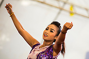 "15 JUNE 2014 - BANGKOK, THAILAND: A dancer performs during a ""Return Happiness to Thais"" party in Lumpini Park in Bangkok. The Thai military junta, formally called the National Council for Peace and Order (NCPO), is sponsoring a series of events throughout Thailand to restore ""Happiness to Thais."" The events feature live music, dancing girls, military and police choirs, health screenings and free food.   PHOTO BY JACK KURTZ"