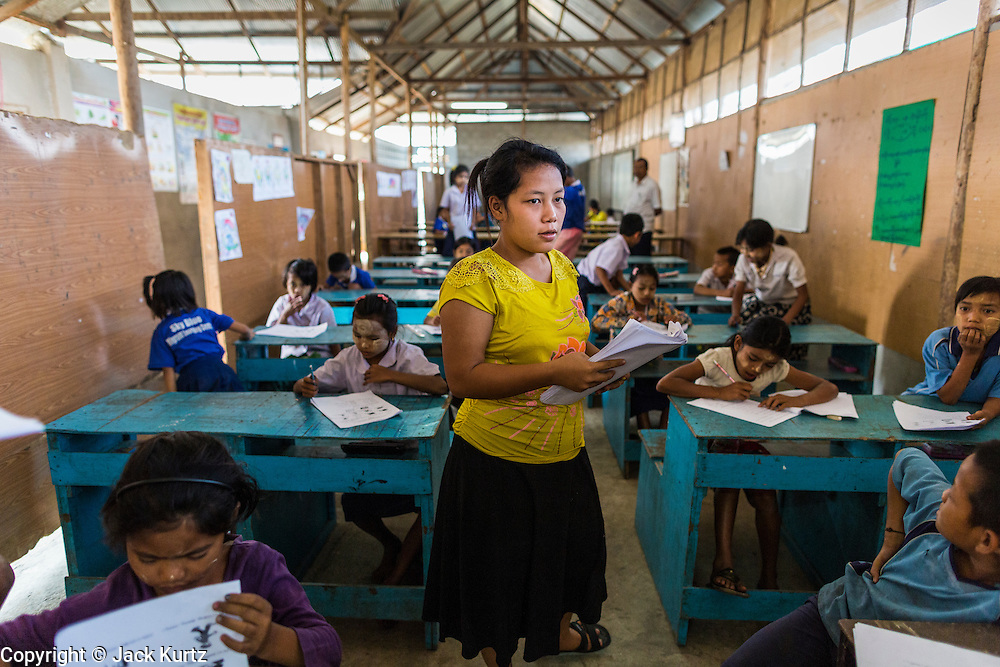 04 MARCH 2014 - MAE SOT, TAK, THAILAND: A teacher collects final exams from students at the Sky Blue School. There are approximately 140 students in the Sky Blue School, north of Mae Sot. The school is next to the main landfill for Mae Sot and serves the children of the people who work in the landfill. The school relies on grants and donations from Non Governmental Organizations (NGOs). Reforms in Myanmar have alllowed NGOs to operate in Myanmar, as a result many NGOs are shifting resources to operations in Myanmar, leaving Burmese migrants and refugees in Thailand vulnerable. The Sky Blue School was not able to pay its teachers for three months during the current school year because money promised by a NGO wasn't delivered when the NGO started to support schools in Burma. The school got an emergency grant from the Burma Migrant Teachers' Association and has since been able to pay the teachers.    PHOTO BY JACK KURTZ