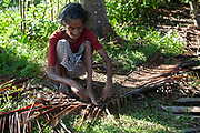 An old woman weaving plants together on 17th November 2009 in the backwaters near Alappuzha aka Alleppey, Kerela, India.