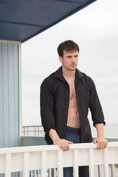 hot man in an open shirt standing on a balcony