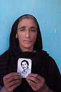 "Fawzia holding a photo of her husband Esmeri. ""I became a widow during the Mujaheddin war , 10 years ago. There was an air raid and my husband was killed by one of the bombs."""