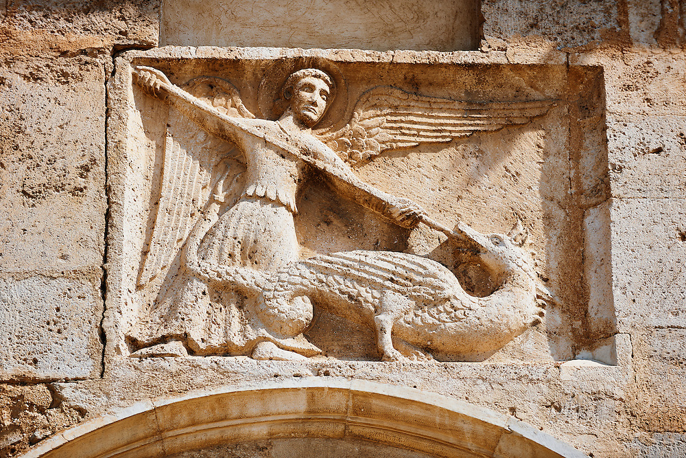 Sculpture of St Michael killing a dragon on the 12th century Romanesque facade of the Chiesa di San Pietro extra moenia (St Peters), Spoletto, Italy .<br /> <br /> Visit our ROMANESQUE SCULPTURE PHOTO COLLECTION for more   photos  to download or buy as prints https://funkystock.photoshelter.com/gallery/Romanesque-Statue-Sculptures-Pictures-Images/G0000ezFHYeF_xRI/C0000YpKXiAHnG2k<br /> If you prefer to buy from our ALAMY PHOTO LIBRARY  Collection visit : https://www.alamy.com/portfolio/paul-williams-funkystock/pietro-extra-moenia-spoleto.html .<br /> <br /> Visit our MEDIEVAL PHOTO COLLECTIONS for more   photos  to download or buy as prints https://funkystock.photoshelter.com/gallery-collection/Medieval-Middle-Ages-Historic-Places-Arcaeological-Sites-Pictures-Images-of/C0000B5ZA54_WD0s