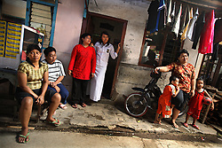Neighbors Suryani, far left, 37, Karsih, in red, 40, and Marniati, on bike, 35, are photographed in Jakarta, Indonesia, April 24, 2006. The women have all had abortions. A woman who has an abortion can get four years in jail while the doctor who performed it can get up to 15 years. Yet 2.3 million abortions are performed in Indonesia every year, many by unskilled practitioners. Thousands of women survive but often with life-long disabilities. It is said by doctors and activists that a woman dies every hour in Indonesia due to unsafe abortions.